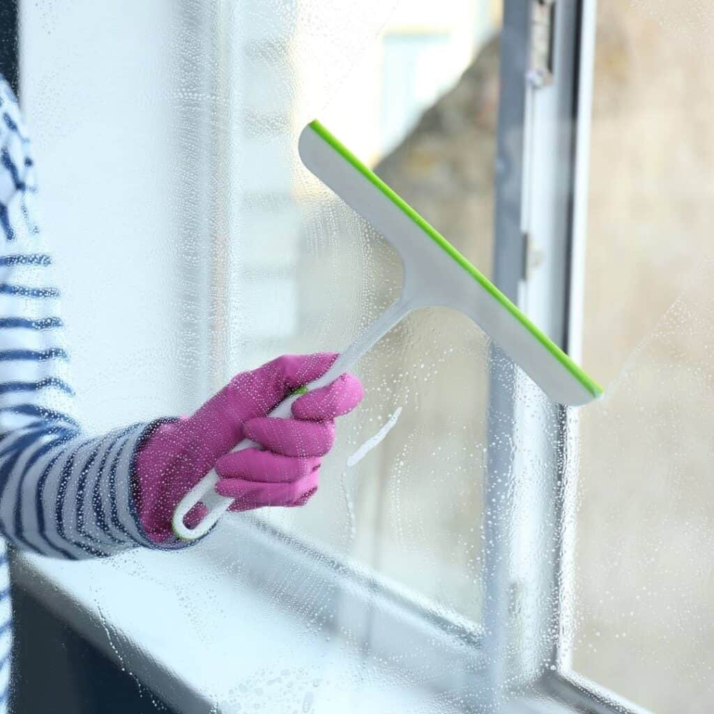 woman using a squeegee to clean the kitchen windows